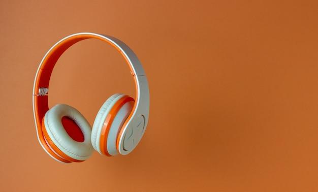Pomarańczowe Słuchawki Na Pomarańczowej ścianie Premium Zdjęcia