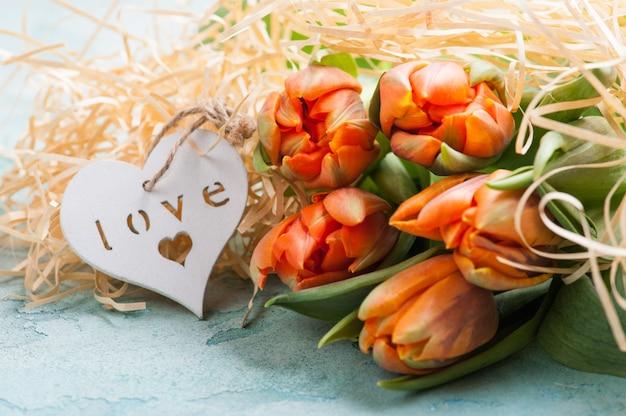 Pomarańczowe tulipany z drewnianym sercem Premium Zdjęcia