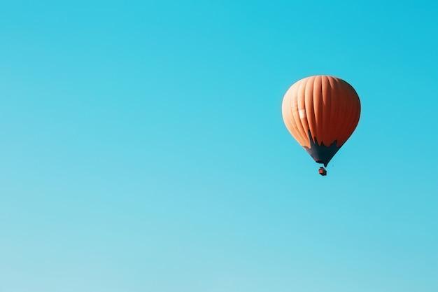 Pomarańczowy balon szybuje na tle błękitnego nieba Premium Zdjęcia