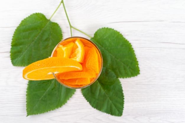 Pomarańczowy Koktajl Z Widokiem Z Góry Ze świeżym Kawałkiem Pomarańczy Wraz Z Zielonymi Liśćmi Na Białym, Chłodzący Napój Koktajlowy Darmowe Zdjęcia
