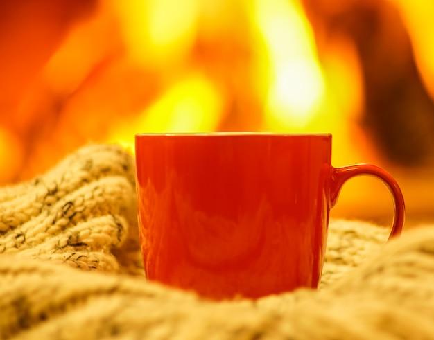 Pomarańczowy kubek na herbatę lub kawę, wełny na tle przytulnego kominka. Premium Zdjęcia