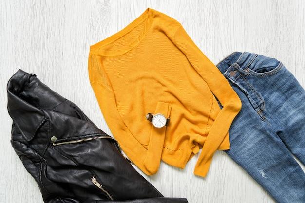 Pomarańczowy sweter, zegarek, czarna kurtka i dżinsy Premium Zdjęcia