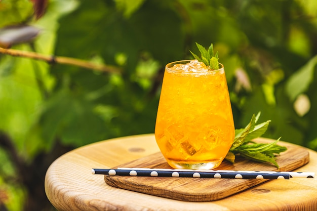Pomarańczowy świeży Napój Z Lodem Na Lata Pogodnym Ogrodowym Tle. Premium Zdjęcia
