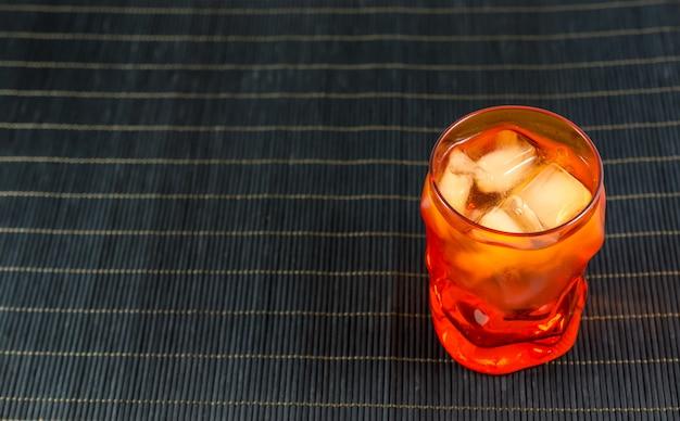 Pomarańczowy Szklankę Wody Z Lodem Na Czarnej Powierzchni Bambusa Premium Zdjęcia