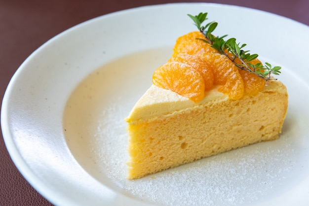 Pomarańczowy Tort Z Pomarańczową Owocową Polewą Na Białym Naczyniu Premium Zdjęcia