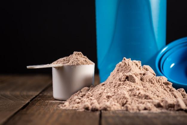 Pomiar miarki białka serwatki na drewnianym stole w celu przygotowania koktajlu mlecznego. Premium Zdjęcia