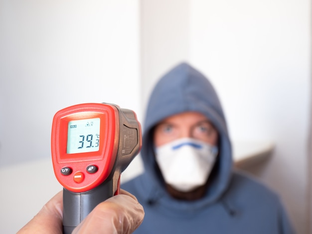 Pomiar Temperatury Człowieka Za Pomocą Miernika Podczerwieni. Wysoka Gorączka, Objaw, Choroba. Premium Zdjęcia