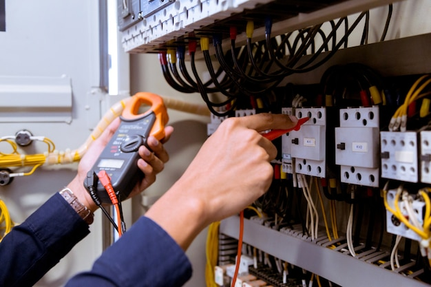 Pomiary Elektryka Za Pomocą Multimetru Sprawdzającego Prąd Elektryczny W Tablicy Sterowniczej. Premium Zdjęcia