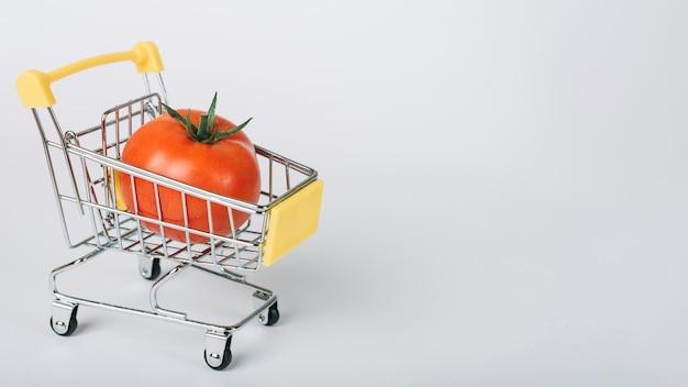 Pomidor w wózek na zakupy na białej powierzchni Darmowe Zdjęcia