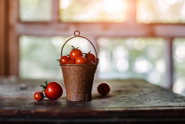 Pomidory czereśniowe w ozdobnym zardzewiałym starym wiadrze na ciemnym rustykalnym. Premium Zdjęcia