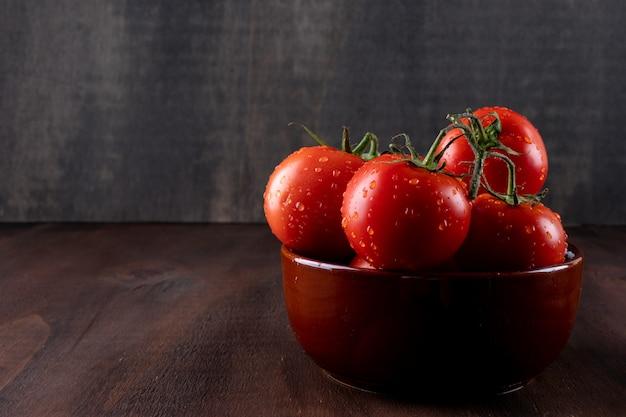 Pomidory świeże I Zdrowotne W Misce Ceramicznej Na Powierzchni Kamienia Brązowego Darmowe Zdjęcia