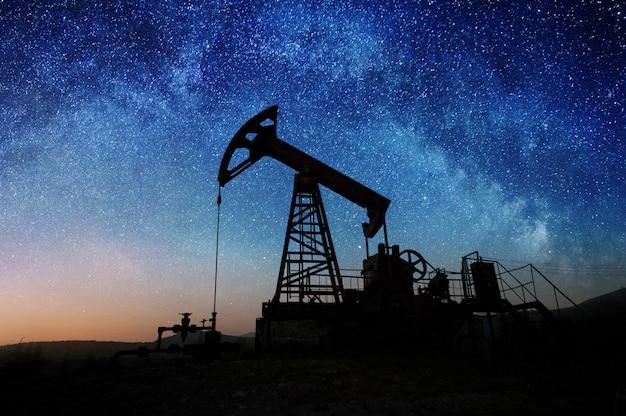 Pompa olejowa na polu naftowym w nocy Premium Zdjęcia