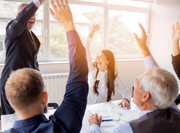 Pomyślna biznes drużyna podnosi ich ręki przy miejscem pracy Darmowe Zdjęcia