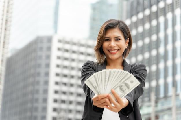 Pomyślna piękna azjatycka biznesowa kobieta trzyma pieniądze dolarów amerykańskich rachunki w ręce, biznesowy pojęcie Darmowe Zdjęcia