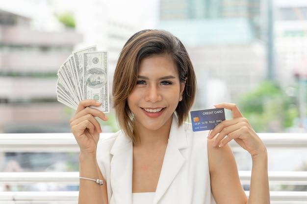Pomyślna piękna azjatycka biznesowa kobieta trzyma pieniądze w dolarach amerykańskich rachunki i kartę kredytową Darmowe Zdjęcia