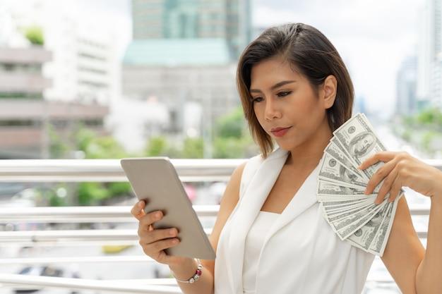 Pomyślna piękna azjatykcia biznesowa młoda kobieta używa mądrze telefon i pieniądze rachunki w dolarach amerykańskich w ręce Darmowe Zdjęcia