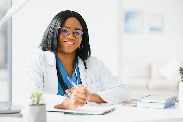 Pomyślny Czarny Lekarz Kobieta Uśmiecha Się W Biurze Premium Zdjęcia