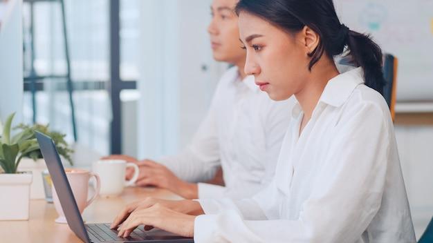 Pomyślny Piękny Wykonawczy Asia Młodego Bizneswomanu Mądrze Przypadkowej Odzieży Dopatrywania Tutorial O Kreatywnie Pomysłach Przy Laptopem Podczas Pracy Procesu W Nowożytnym Biurowym Miejscu Pracy. Darmowe Zdjęcia