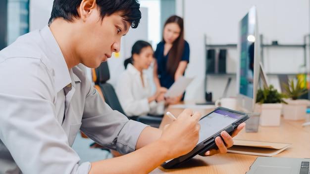 Pomyślny Wykonawczy Asia Młodego Biznesmena Mądrze Przypadkowy Odzież Rysuje, Pisze I Używa Pióro Z Cyfrowym Pastylki Komputerowym Główkowaniem Inspiraci Rewizi Pomysłów Pracuje Proces W Nowożytnym Biurze. Darmowe Zdjęcia