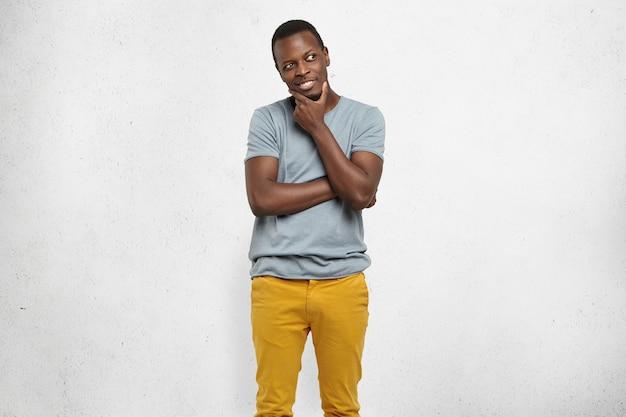 Pomysłowy Przystojny Afroamerykański Mężczyzna Odwracający Wzrok Z Chytrym Uśmiechem, Trzymając Dłoń Na Brodzie Darmowe Zdjęcia