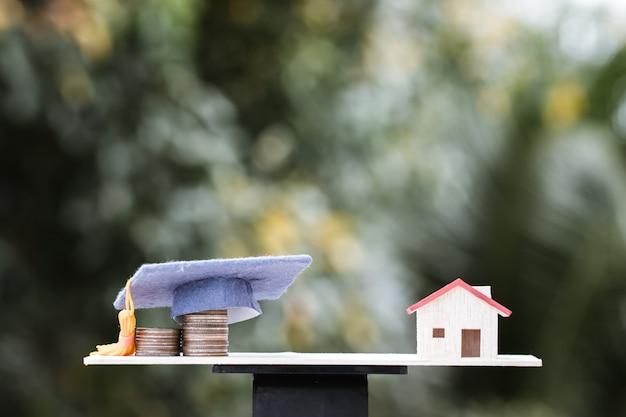 Pomysły Na Inwestycje I Edukację: Dropshipping Monet Do Czapki Graduation Na Bilansie Drewna Z Modelem Domu. Koncepcja Kształcenia Uniwersytetu Wymaga Ratowania Pieniędzy, Przyniesie Stopień Domowy. Premium Zdjęcia