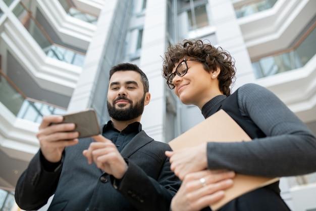 Poniżej Widok Odnoszących Sukcesy Specjalistów Od Marketingu Korzystających Ze Smartfona Podczas Oglądania Statystyk W Social Media Premium Zdjęcia