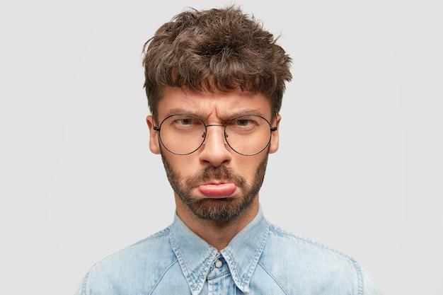 Ponury Mężczyzna Z Zarostem W Torebce Usta I Niezadowolony Patrzy W Kamerę, Czuje Się Urażony Po Usłyszeniu Skierowanych Do Niego Złych Słów, Nosi Dżinsową Koszulę Darmowe Zdjęcia