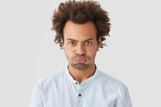 Ponury Posępny Mężczyzna Z Kręconymi Włosami, Zarostem, Niezadowolonym Wyrazem Twarzy, Wyrażający Negatywne Emocje, Ubrany W Białą Koszulę Darmowe Zdjęcia