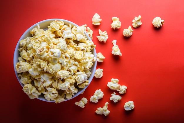 Popcorn w białym bowl na czerwonym tle, selektywne fokus na popcorn w białym bowl Premium Zdjęcia