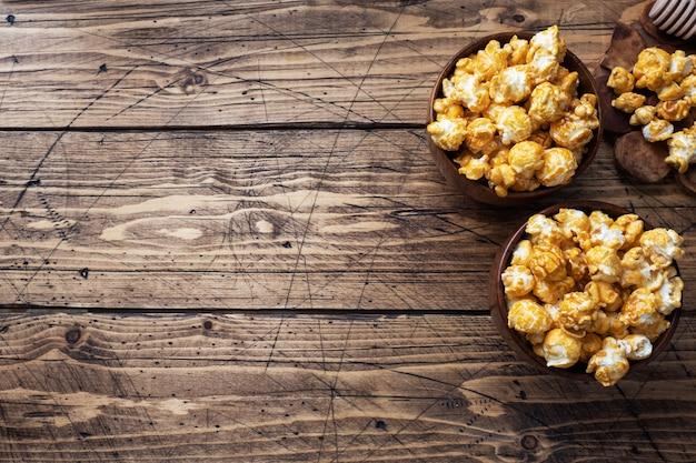 Popcorn W Polewie Karmelowej W Drewnianych Talerzach Na Rustykalnym Stole. Premium Zdjęcia