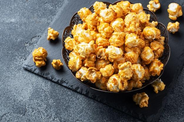 Popcorn W Polewie Karmelowej W Talerzu Na Ciemnym Betonowym Stole. Premium Zdjęcia