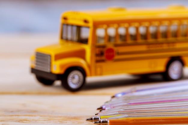 Popiera Szkół Dostaw Barwioni Ołówki Bawją Się żółtego Autobus Szkolnego Na Drewnianym Tle Premium Zdjęcia