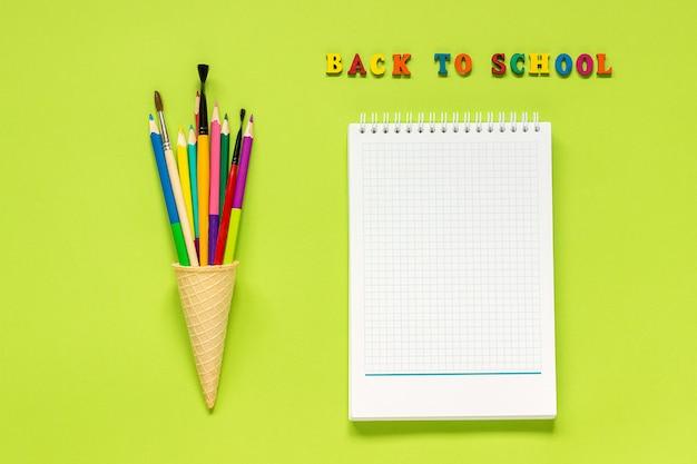 Popiera szkoły i coloured ołówka paintbrush w gofra lody rożku i notatniku na zielonym tle. Premium Zdjęcia