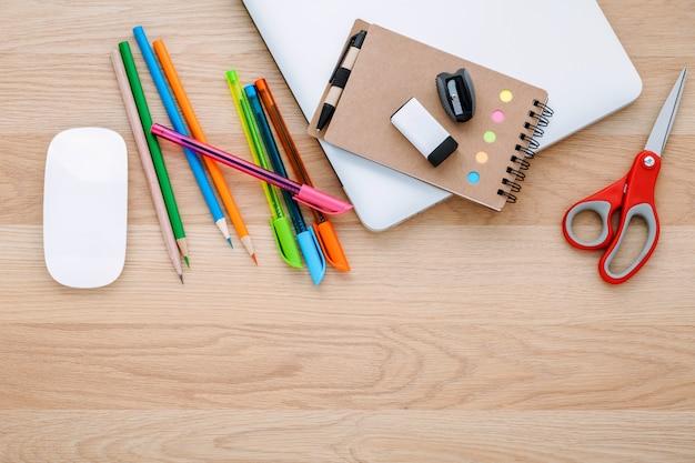 Popiera szkoły pojęcie z szkolnymi dostawami na drewnianym stole. Premium Zdjęcia