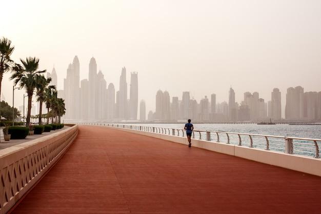Poranny bieg, mężczyzna biegnie wzdłuż drogi z pięknym widokiem na dubaj. Premium Zdjęcia