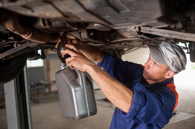 Portait mechanika samochodowego odprowadzającego olej silnikowy pod zniesionym samochodem Premium Zdjęcia