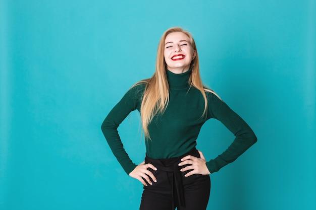 Portait szczęśliwa blondynki kobiety pozycja na błękitnym tle Premium Zdjęcia