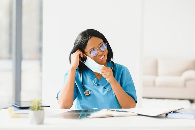 Portret African American Piękna Kobieta Lekarz W Masce Medycznej Patrząc Na Kamery. Zamknij Się Kobieta Lekarz W Ochronie Dróg Oddechowych. Premium Zdjęcia