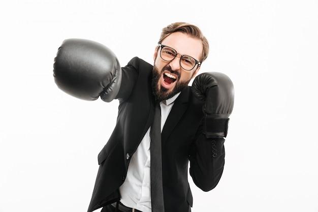 Portret Agresywny Biznesmen Krzyczy W Czarnym Garniturze I Okularach, Jednocześnie Wykrawając W Rękawice Bokserskie, Na Białym Tle Nad Białą ścianą Premium Zdjęcia