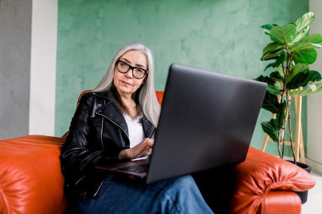 Portret Atrakcyjnej Uśmiechniętej Starszej Kobiety W Okularach I Czarnej Skórzanej Kurtce, Pozowanie Do Aparatu, Siedząc W Wygodnym Czerwonym Fotelu I Używając Swojego Laptopa Premium Zdjęcia
