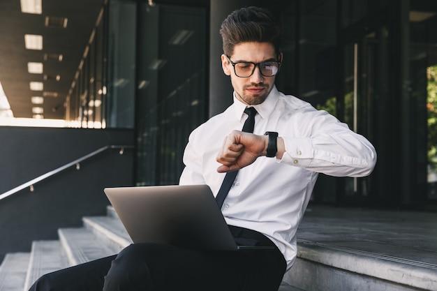 Portret Atrakcyjny Biznesmen, Ubrany W Formalny Garnitur, Siedząc Na Zewnątrz Budynku Ze Szkła Z Laptopem I Patrząc Na Zegarek Na Rękę Premium Zdjęcia