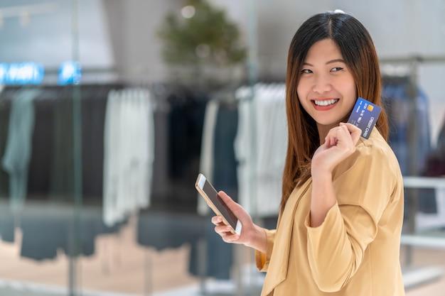 Portret Azjatycka Kobieta Używa Kredytową Kartę Z Mądrze Telefonem Komórkowym Dla Online Zakupy W Wydziałowym Sklepie Premium Zdjęcia