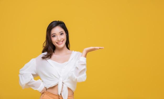 Portret Azjatycka Piękna Szczęśliwa Młoda Kobieta Ono Uśmiecha Się Rozochoconą I Patrzeje Kamerę Odizolowywającą Na żółtym Pracownianym Tle Premium Zdjęcia
