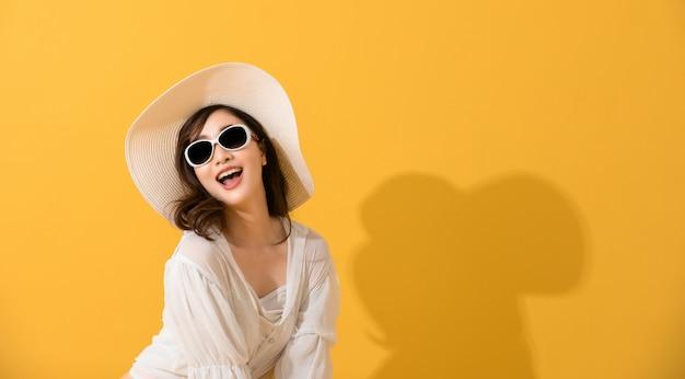 Portret Azjatycka Piękna Szczęśliwa Młoda Kobieta Z Okularami Przeciwsłonecznymi, Kapeluszowy Ono Uśmiecha Się Rozochocony W Lecie I Patrzeć Kamerę Odizolowywającą Na żółtym Pracownianym Tle. Premium Zdjęcia