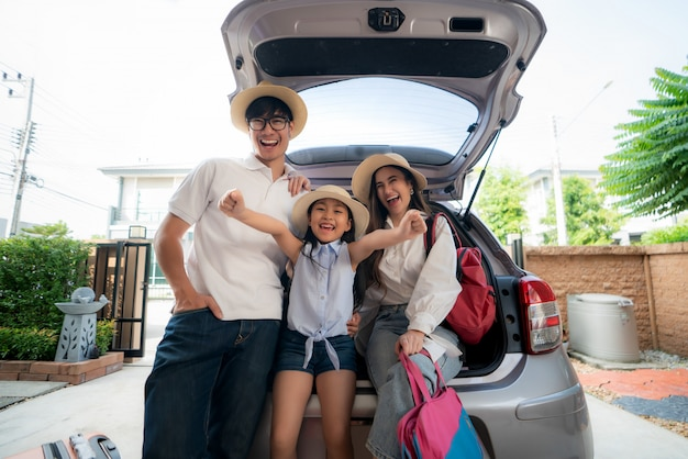 Portret azjatycka rodzina z ojcem, matką i córką, patrzeje szczęśliwy podczas gdy przygotowywający walizkę w samochód na wakacje. Premium Zdjęcia