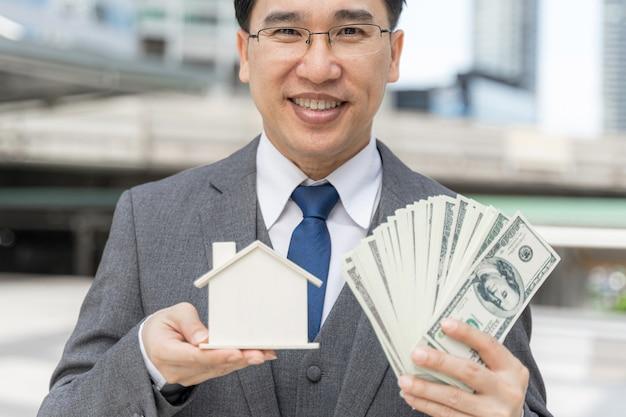 Portret Azjatycki Biznesowy Mężczyzna Trzyma Pieniądze Dolary Amerykańskie I Model Domu W Dzielnicy Biznesowej Darmowe Zdjęcia
