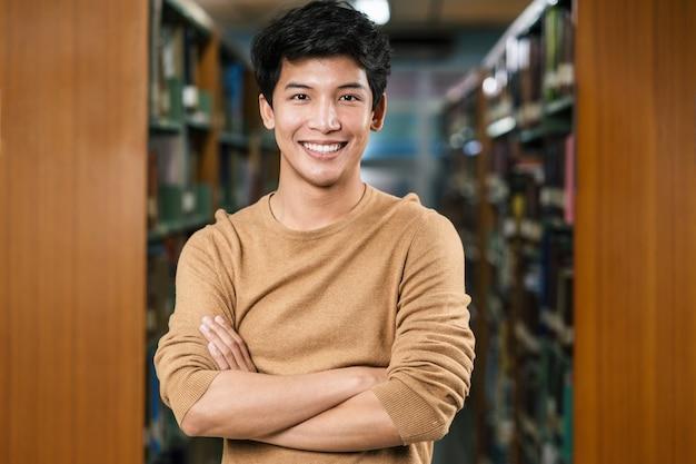 Portret Azjatyckich Młodych Studentów W Dorywczo Garnitur W Bibliotece Uniwersytetu Lub Kolegium Na Tle Półki Z Książkami Premium Zdjęcia