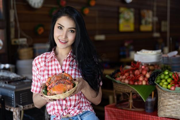 Portret Azjatykcie Kobiety Z Lejącym Się Krabem Na Ręce W Amphawa Rynku Premium Zdjęcia