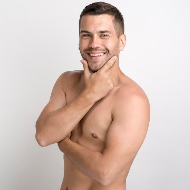 Portret bez koszuli uśmiechnięty młody człowiek utrzymuje rękę na podbródku i patrzeje kamerę Darmowe Zdjęcia
