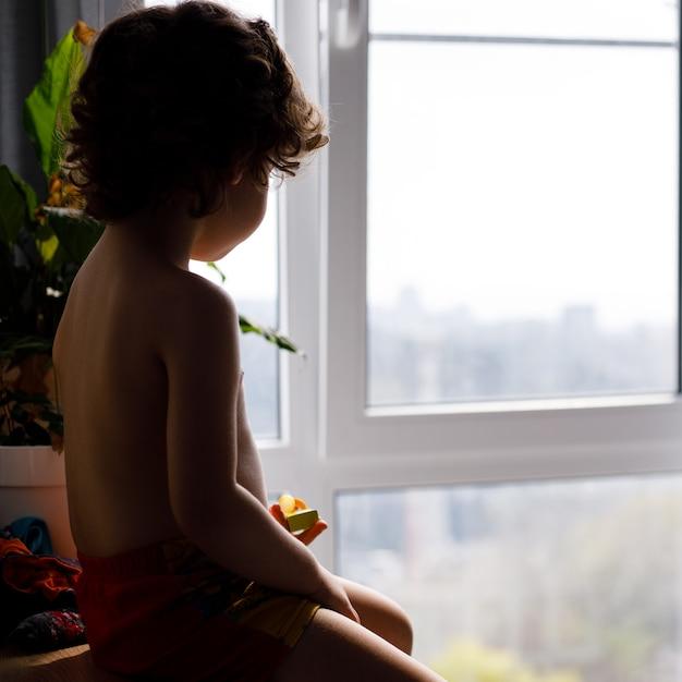 Portret Białego Dziecka Rasy Kaukaskiej Chłopiec W Domu Patrząc Z Okna Na Zewnątrz. Widok Z Tyłu. Dziecko Czeka Na Kogoś Premium Zdjęcia